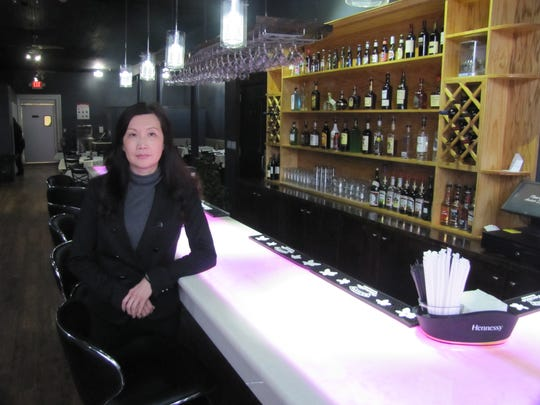 Pailing Yang, manager, stands by the bar at Thai Asian