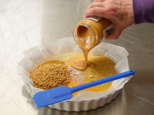 Spread baking parchment in a pan. Mix chicken scratch, coarse corn meal and hulled millet to liquid lard. Add crushed egg shells and warmed peanut butter.