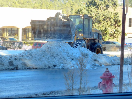 A plow shovels snow to keep lanes open on Sudderth