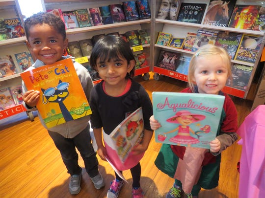 Eager Readers: Terrence LeGall of Linden, Akshara Shankar of Edison and Julia Gonnella of Somerset, Junior Kingergarten students at The Wardlaw-Hartridge School in Edison, proudly display the books they purchased at the Wardlaw-Hartridge Parents' Association Book Fair in the Oakwood Room. All W-H students were invited to the annual Book Fair, which included books for all ages and provided some wonderful winter reading for the school community.