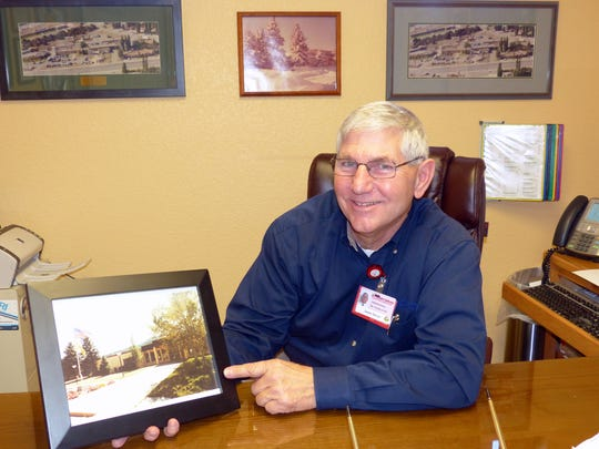 Lincoln County EMS Director Jim Stover holds a photograph of the Lincoln County Medical Center before a renovation. In back are other photos of the county-owned hospital before, during and after construction projects.