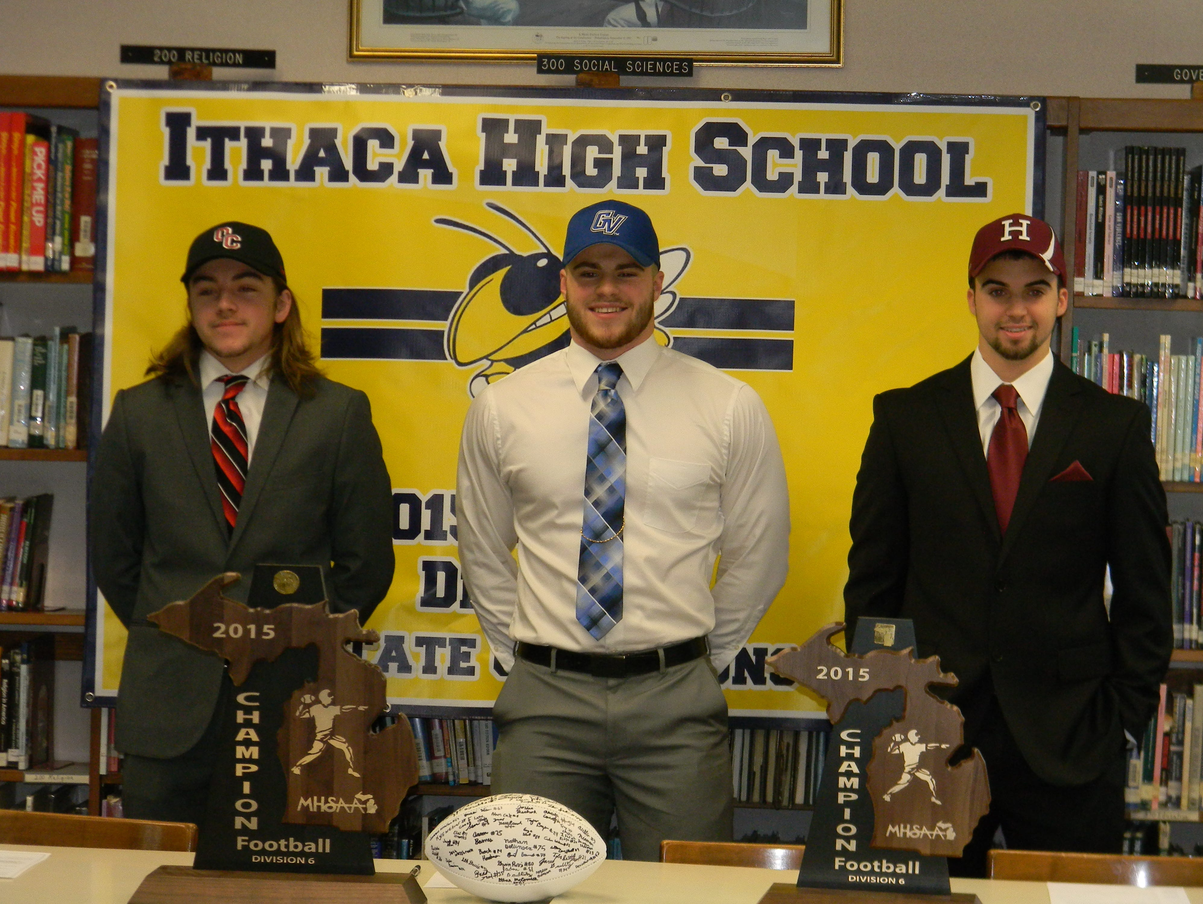 Ithaca seniors Grant Gimmey, left, Jace Demenov, center, and Jake Smith pose for a picture after signing with their respective colleges Wednesday morning. Gimmey is headed to Olivet College, Demenov to Grand Valley and Smith to Harvard.