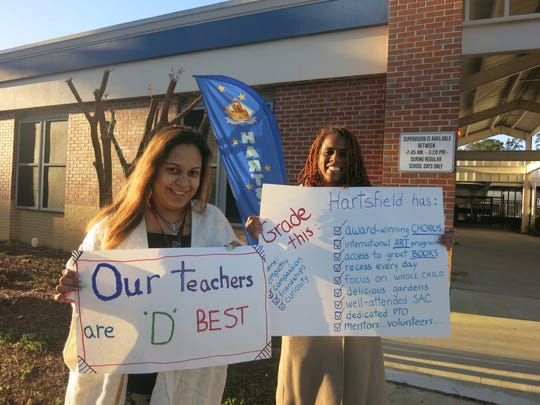 Parents of Hartsfield Elementary students stand by teachers during a school grades protest.