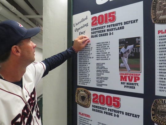 Brett Jodie looks at the decal covering the reveal of the Somerset Patriots' sixth championship ring.