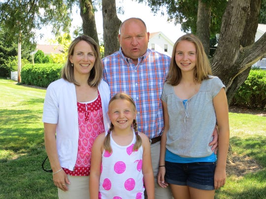 Jon and his wife, Jennifer, pose with their two daughters:
