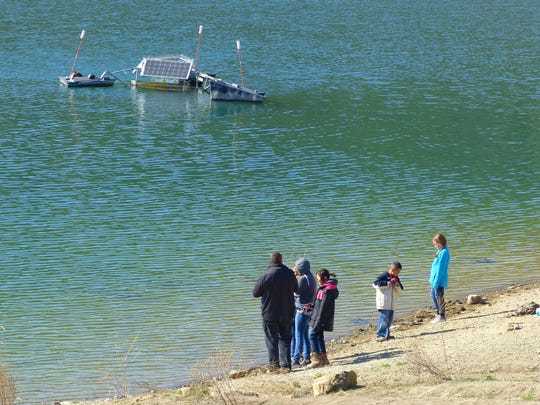 A family enjoys Grindstone Reservoir, which is fed by the snow pack runoff from the mountains into the Rio Ruidoso. The solar aerator at rop left balances the oxygen in the water and helps maintain quality.