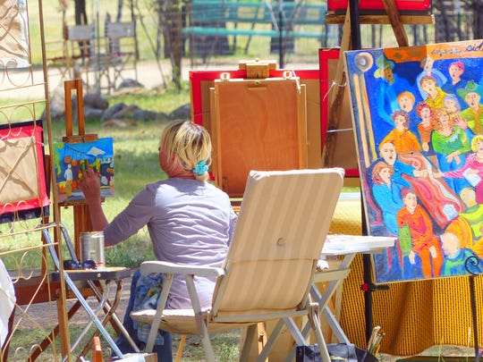 An artist enjoys a day in the sunshine at the Two Rivers Arts and Crafts Fair at Wingfield Park near midtown.