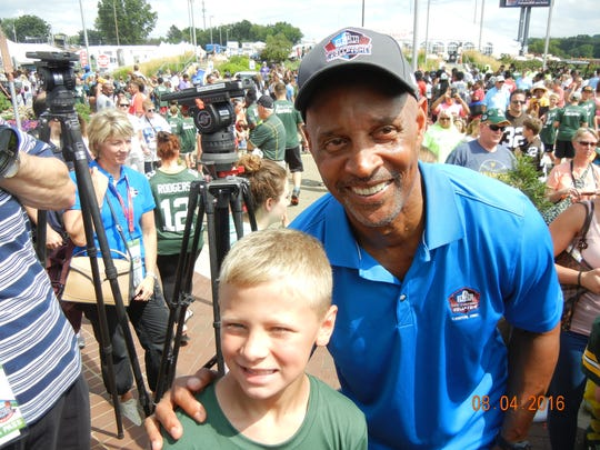 """Brett Rybarczyk, 8, of Cleveland, poses with Hall of Fame player James Lofton during the Pro Football Hall of Fame's """"First Play"""" event in Canton, Ohio."""