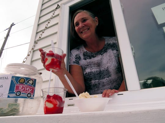Carol Schaefer of Historic Newburgh serves homemade vanilla ice cream with strawberry topping from the Newburgh Kiwanis booth at this year's Fiddler Fest.
