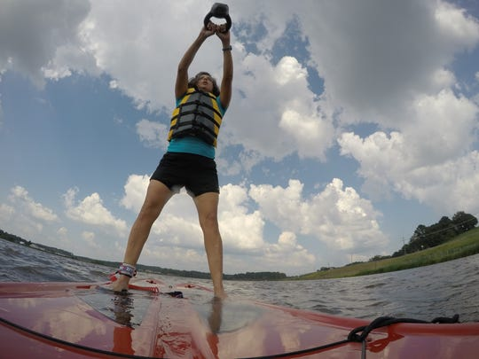 Kettlebell swings can be performed on a stand-up paddle board on the water.