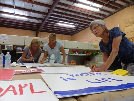 Gloria, of Sarasota, who did not give her last name, draws up a sign against the Dakota Access Pipeline in the Juanita Osceola Center on Sept. 13. Demonstrators showed off the signs at Collier Boulevard and City Gate Drive to raise awareness about the Dakota Access Pipeline. Since April 1, people from across the country have united at Standing Rock to stop the pipeline.
