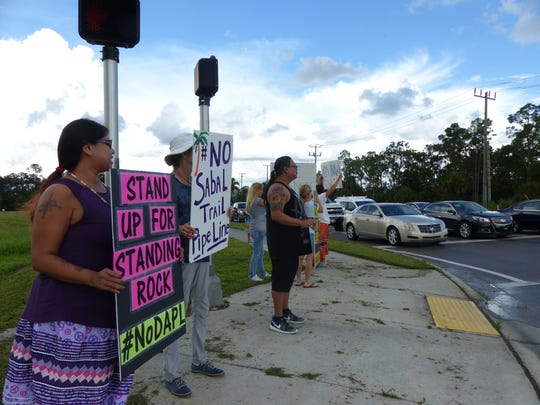 """Nelda Melton, of Big Cypress, holds a sign reading """"Stand Up for Standing Rock."""" She was one of several demonstrators standing at Collier Boulevard and City Gate Drive on Sept. 13 to raise awareness about the Dakota Access Pipeline. Since April 1, people from across the country have united at Standing Rock to stop the pipeline."""