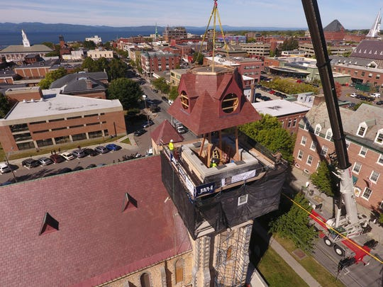 The first of three sections of a replacement steeple are hoisted into place Monday at the College Street Congregational Church in Burlington.