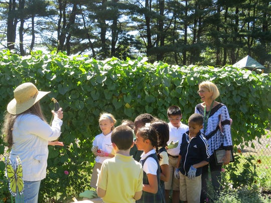 Third grade students join their teacher, Katherine Heiss in the garden for a brief presentation by Bonnie Farrell of Fords.