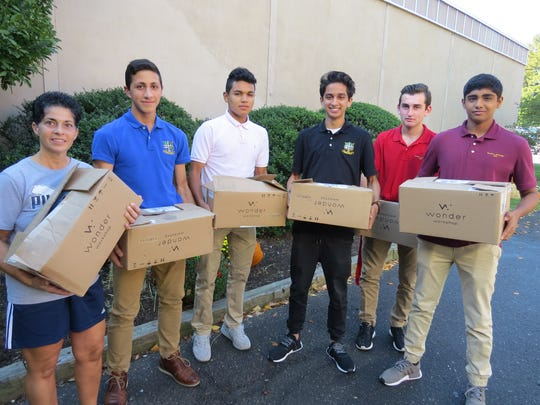 Lending a hand... Dawn Francavilla of Somerset, Director of Student Life at The Wardlaw-Hartridge School in Edison, is joined by juniors Kevin Nader of Bernardsville, Ovidio Chavez of Elizabeth, Raj Raval of South Plainfield, Jack Sartor of Green Brook and Rohan Arvindh of Woodbridge as they prepare to load boxes with more than 800 food items collected during a food drive for Hands of Hope in Edison.