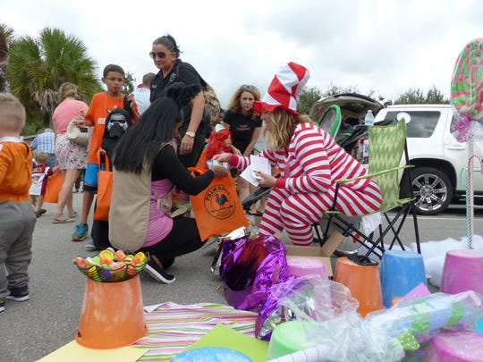 Chrissy Fleischer gets into the Halloween spirit by giving out candy during a trunk-or-treat event at Primrose School of Naples on Oct. 28, 2016. She was one of about a dozen parents offering candy out of their car's trunks.
