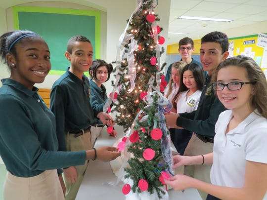 Season Of Giving… Eighth grade students at The Wardlaw-Hartridge School in Edison visit the Giving Tree, from which they selected ornaments with gift suggestions for autistic children attending the Crossroads School in Westfield. The gifts will be delivered to the school for autistic children next week. Pictured, from left: Nadia Valcourt of South Plainfield, Kyler Montague of West Orange, Emma Jacobson of Metuchen, John Papetti of Elizabeth, Sara Reiss of Fords, Sara Piao of Edison, Michael Peruzzo of Westfield and Olivia DeSousa of Iselin.