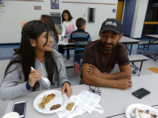 Cindy Godinez, 13, talks to her dad, Juan Godinez, as they share a free meal at East Naples Middle School on Dec. 15, 2016. They were one of many families that grabbed groceries for the week from Collier Harvest.