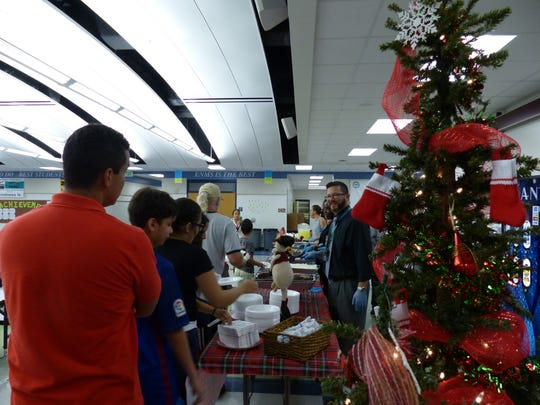 East Naples Middle School Principal Darren Burkett greets, and serves food to students and their families on Dec. 15, 2016.