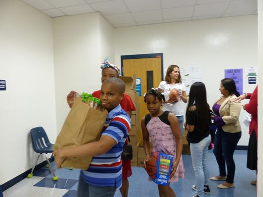 Students from East Naples Middle grab a week's worth of groceries, and ham, from Collier Harvest volunteers on Dec. 15, 2016.