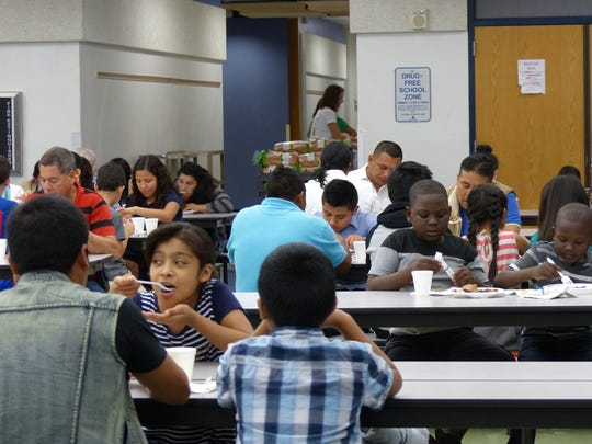 Families enjoy a Christmas meal at East Naples Middle School on Dec. 15, 2016 as part of Collier Harvest's new initiative, Collier CAN!