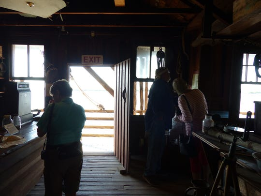 Gary McMillin, right, shows a visitor an artifact inside the Smallwood Store on the Chokoloskee Island on Dec. 22, 2016.