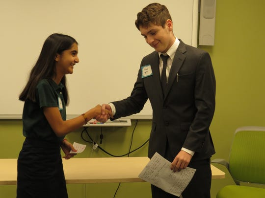 Anna Razvi pf Somerset and Noah Apter of Springfield shakes hands before making their respective arguments.