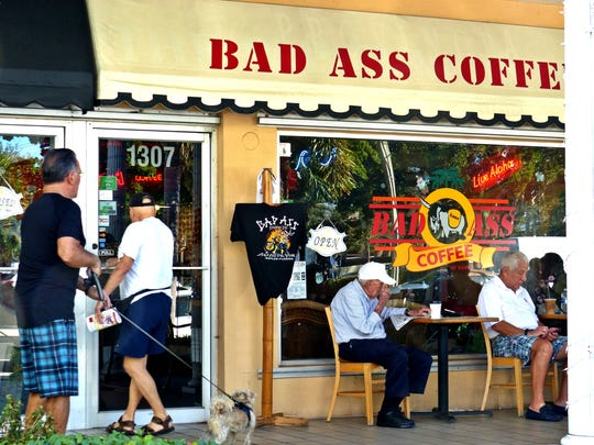 Patrons enter or sit outside the Bad Ass Coffee Company on Third Street in Naples.