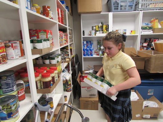 John Paul II fourth grader Ava Arnett helps to stock shelves at the food pantry with supplies purchased by Union County Farm Bureau.