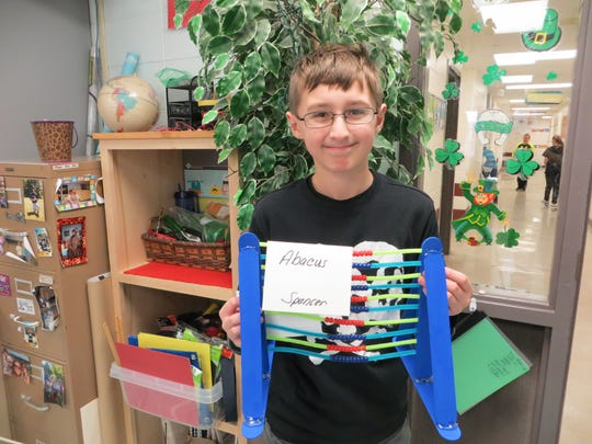 Spencer Oberg creates an abacus at ELG Middle School.