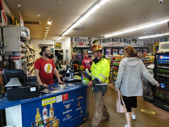 Nick Braun, assistant manager at Lake Liquor & Sporting Goods, greets customers as they come to shop.