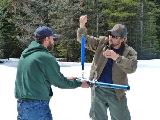 Matthew Herndon, left, and Jake Fitzgerald, inspect the weight of a snow sample on Monday at Big Springs within the Lassen National Forest.
