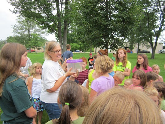 Kathy McGrath and children release three monarch butterflies