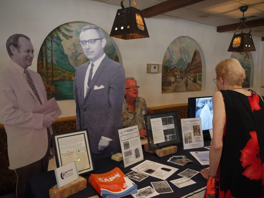 Chris Schroder, seated at the Cape Coral Historical Society's table, greets Beverly McElroy during the fourth Cape Coral Early Residents' Reunion, held April 9 at the German-American Social Club.