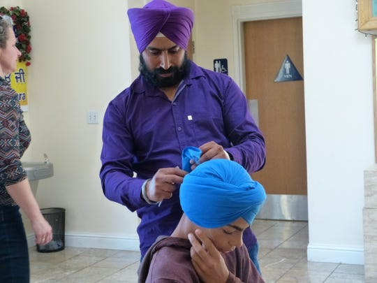 Gurdip Singh, 37, of Cottonwood ties a turban for Brendan Pickett, 14.