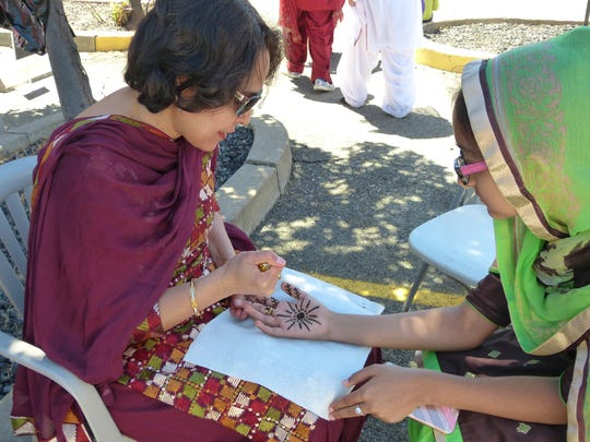Women have henna designs put on their hands at the