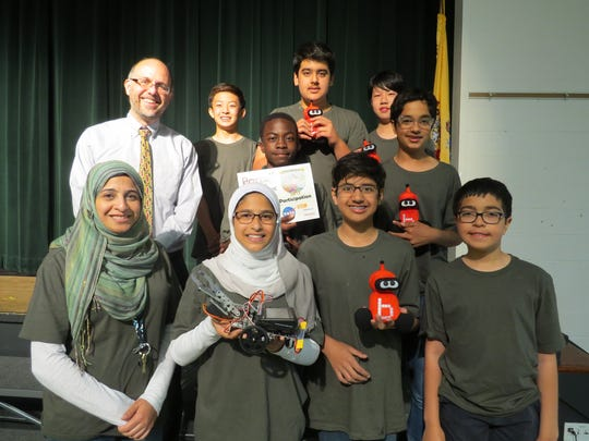The Robotics team proudly displays its robot and award