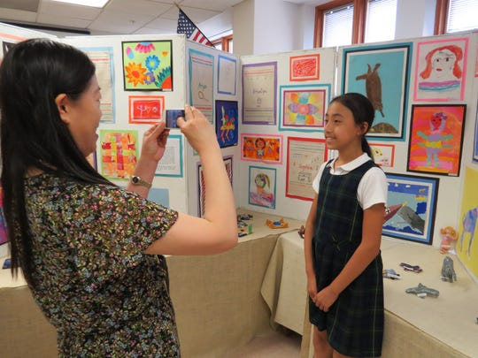 Fifth-grader Hannah Yin of Scotch Plains poses for a photo in front of her artwork at the Lower School Art Show.