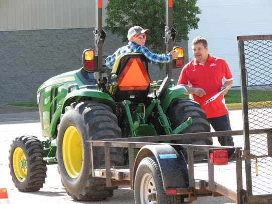 This photo taken May 31, 2017, shows Aaron Yoder, right, of the University of Nebraska Medical Center's Central States Center for Ag Safety and Health in Omaha, giving backing up advice to Alex Bartlett, 14, of Cozad, Neb., during a tractor driving test on the Buffalo County Fairgrounds. (Lori Potter /The Daily Hub via AP)