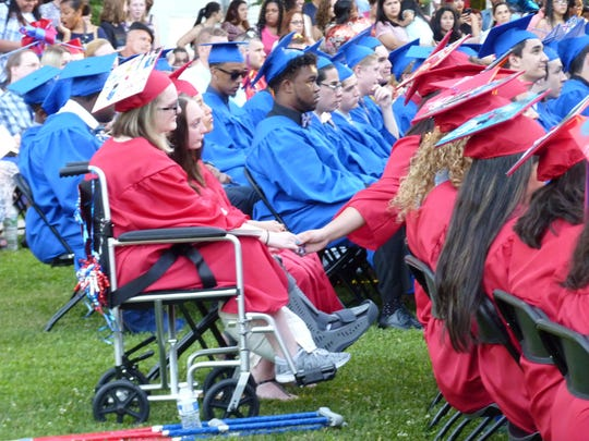 Destiny Lightfoot holds the hand of a fellow classmate at the 2017 Dunellen High School graduation ceremony.