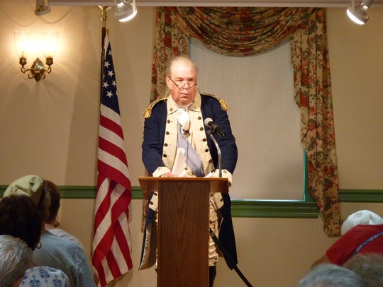 A George Washington re-enactor speaking inside the