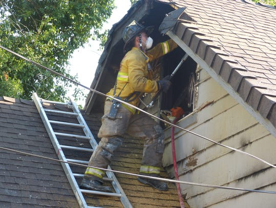 A Redding firefighter inspects the attic of a Magnolia