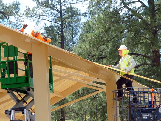 A worker slides a board up to another carpenter working on the pavilion roof in Wingfield Park.