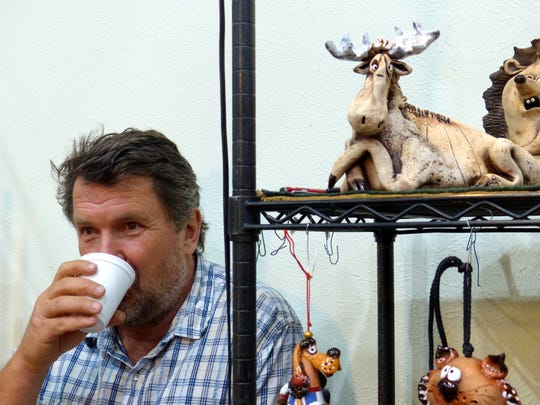 Gint Sabaliauskas sips some coffee as his comical creatures watch at the booth he shared with Regina Sabaliauskas at the art festival.