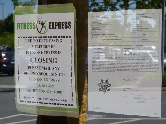 A message to its members, as well as an eviction restoration notice, are posted on the front door at the closed Fitness Express gym at the Mt. Shasta Mall in Redding.