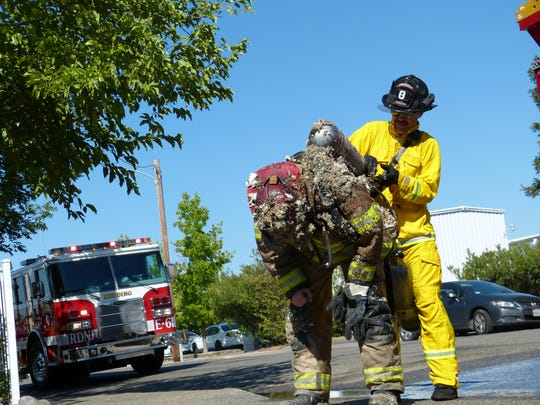 Redding firefighter Mike Ham (right) changes out the