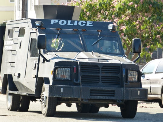 A SWAT team armored truck leaves the scene of a reported
