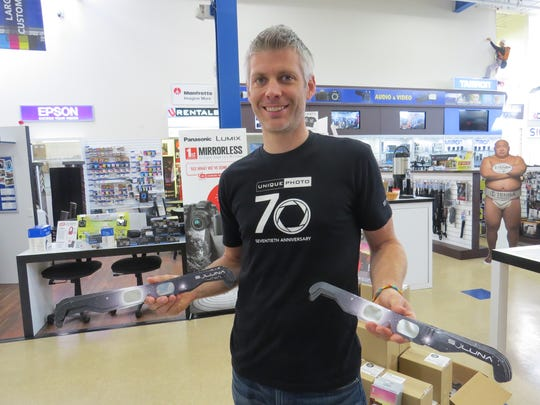 Unique Photo's Scott Farestad holds pairs of solar eclipse glasses available at the Fairfield store.