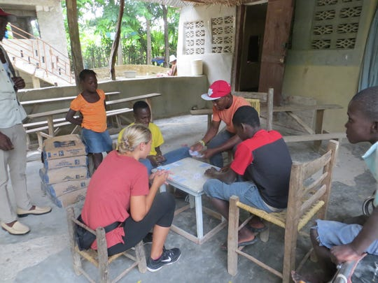 Katrina Pokorny plays a card game with residents during her mission trip to Haiti from Aug. 21 through 27.