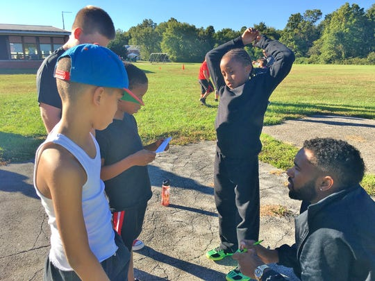 Let Me Run assistant coach Roderick Henry talks to fourth- and fifth-graders at Carrie Downie Elementary School.